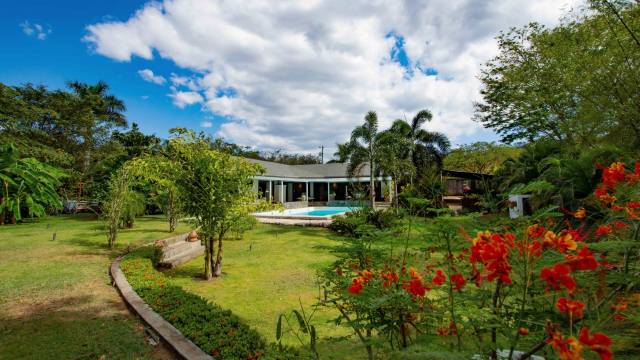 Home for sale with a swimming pool in a roomy tropical garden bordered by a brook...